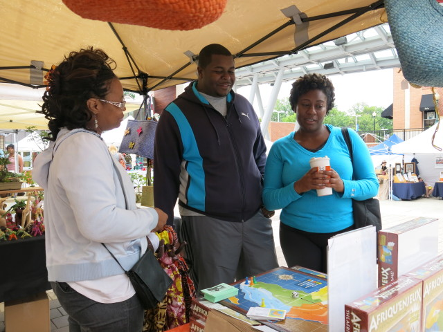 Paulette Mpouma show The Africa Memory game to potential buyers at the Farmers Market in Silver Spring, Maryland. (Photo by Rosanne Skirble/VOA)