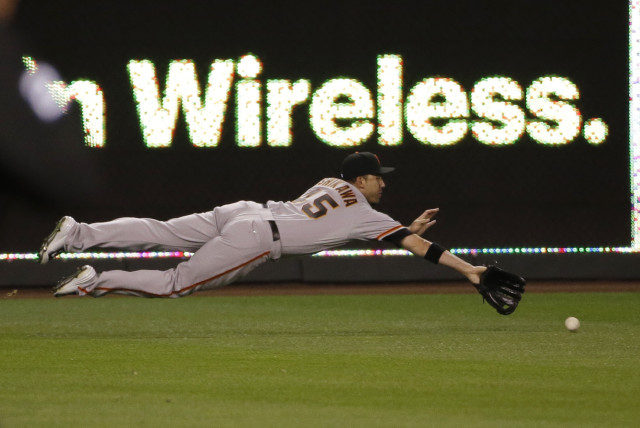San Francisco Giants Travis Ishikawa dives for a ball during the first inning of Game 2 of baseball's World Series, Oct. 22, 2014, in Kansas City, Mo. (AP Photo)