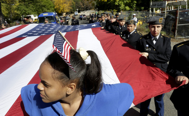 High school student Yomeidi Jose, 16, of Boston, wears a flag on her head while assisting other JROTC students in supporting an oversized American flag during a Columbus Day Parade in Boston, Oct. 12, 2014. (AP Photo)