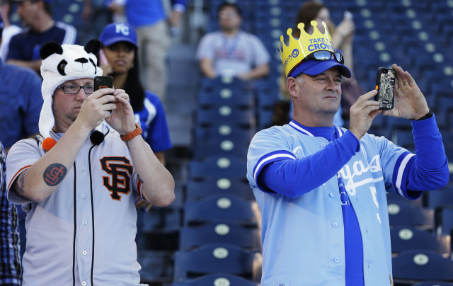 A San Francisco Giants and Kansas City Royals fans take cell phone photos before Game 1 of baseball's World Series between the Kansas City Royals and the San Francisco Giants, Oct. 21, 2014, in Kansas City, Mo. (AP Photo)