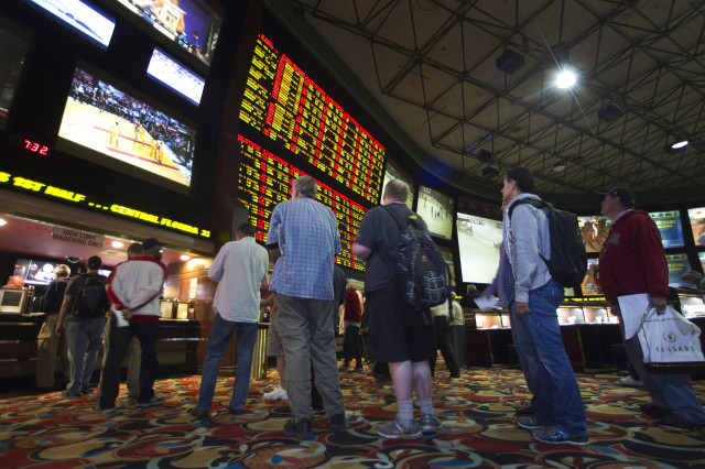 People wait in line to place bets on Super Bowl XLVIII at the Las Vegas Hotel & Casino Superbook in Las Vegas, Nevada Jan. 23, 2014.