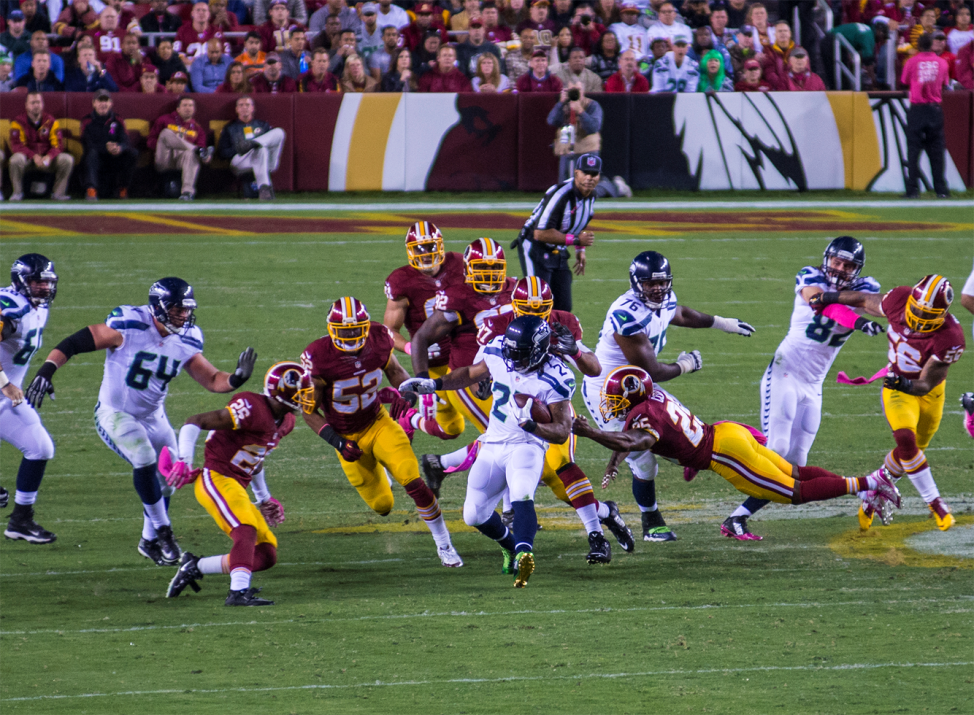 The defending team, the Washington Redskins, tries to stop the offense of the Seattle Seahawks from moving the ball down the field. (VOA / Frank Mitchell)