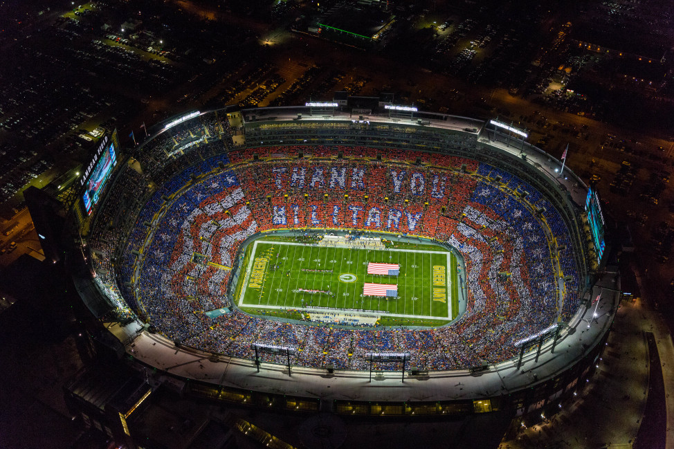 Football fans hold up cards before commemorating veterans before an NFL football game on Nov. 9, 2014, in Green Bay, Wisconsin. (AP Images for USAA)