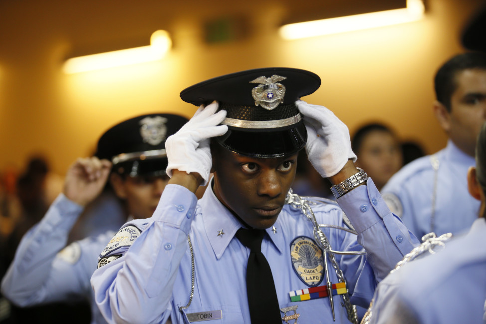 An LAPD cadet commander adjusts his hat before the LAPD cadet program graduation on Nov. 22, 2014, in Los Angeles. Police officers in the United States earn an average annual salary of $58,720. (AP Photo)