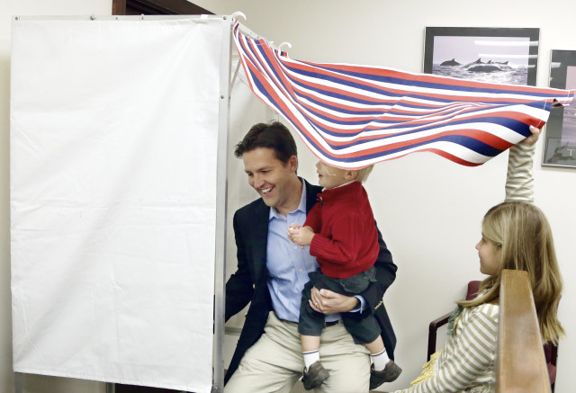 Republican Senate candidate Ben Sasse enters the voting booth with his son Breck, as daughter Alexandra holds the curtain open, during early voting in Fremont, Nebraska, Oct. 31, 2014. (AP Photo)