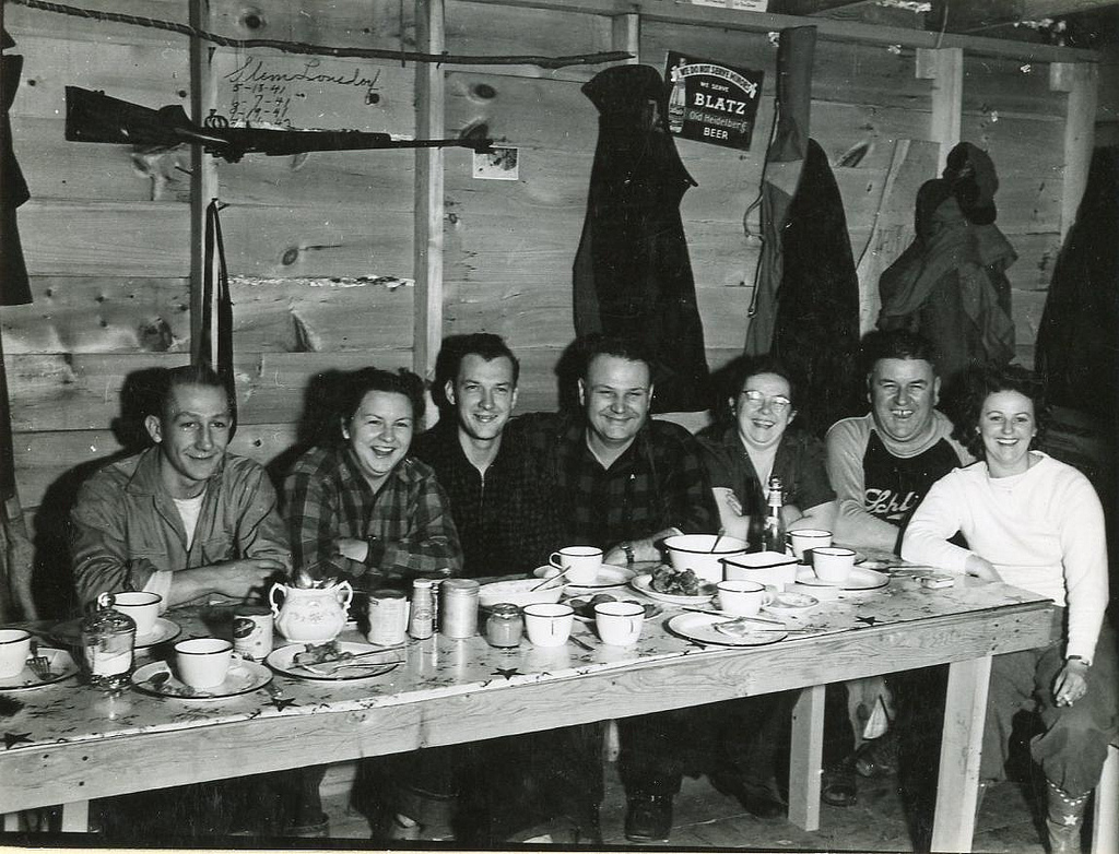 A group of deer hunters sit down for dinner in 1943 at a hunting cabin in Florence County, Wisconsin. Photo courtesy Wisconsin Department of Natural Resources, via Flickr)