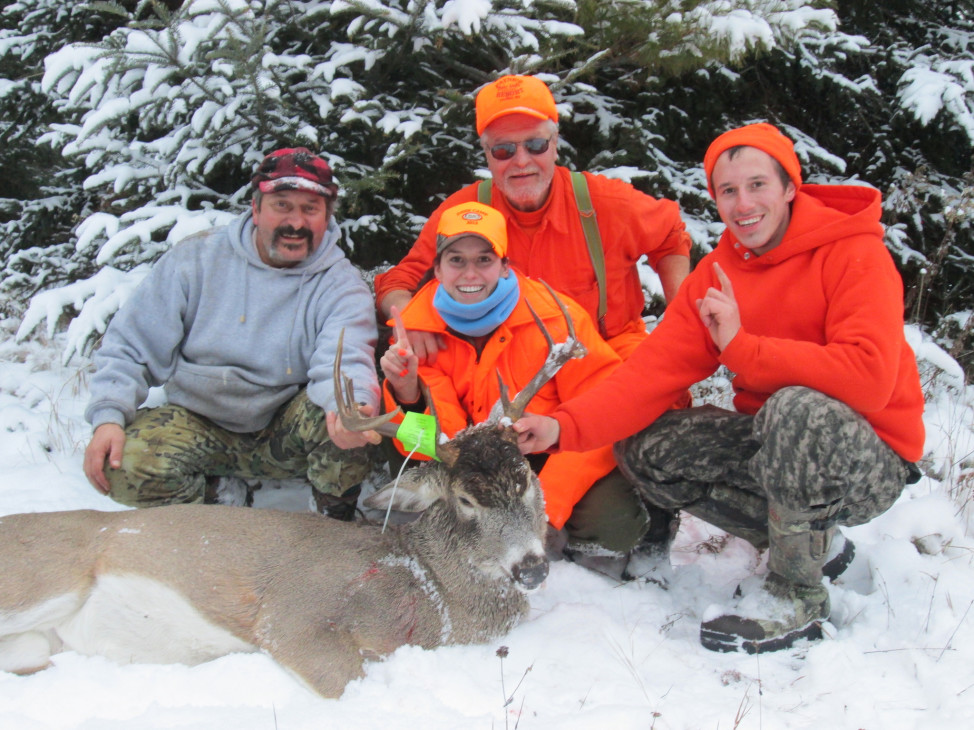 A hunter poses with her first deer. With her are  her father, grandfather and cousin – three generations of hunters. (Photo courtesy Wisconsin Department of Natural Resources, via Flickr)