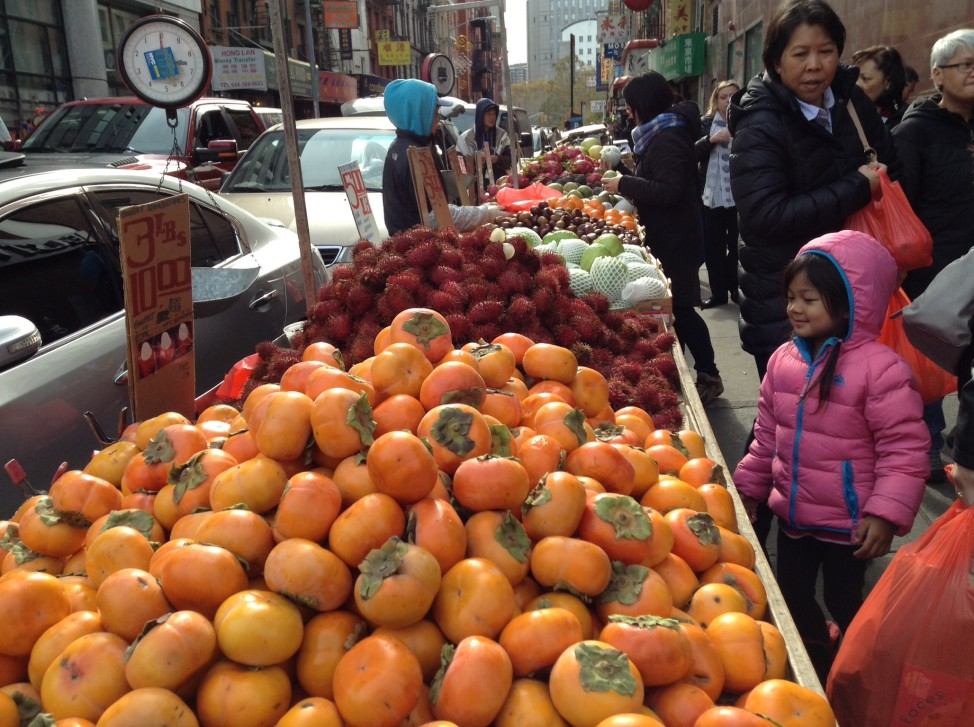 A fruit seller in New York's Chinatown. After English and Spanish, Chinese is the most commonly spoken language in the state.