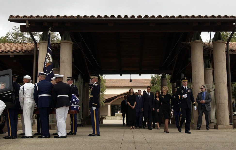 The casket carrying the body of former President Ronald Reagan is loaded into a hearse as Nancy Reagan and her family are escorted from the Ronald Reagan Presidential Library in Simi Valley, California, June 9, 2004. (AP Photo)