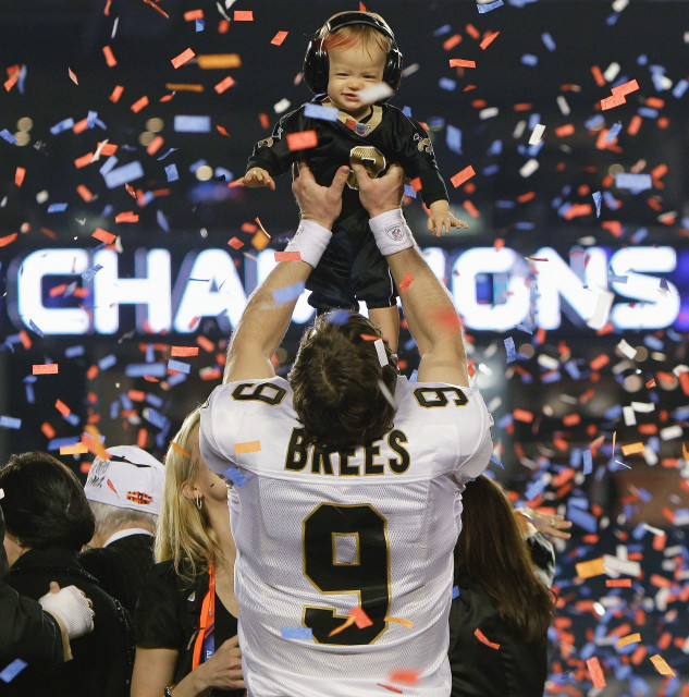 New Orleans Saints quarterback Drew Brees (9) holds his son Baylen after defeating the Indianapolis Colts 31-17 in Super Bowl XLIV, Feb. 7, 2010 , in Miami. (AP Photo)