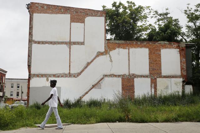A woman walks through a blighted neighborhood, July 11, 2013, in Philadelphia. (AP Photo)