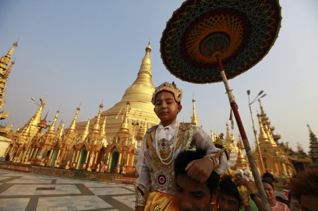 "A boy rides on the shoulders his family members as they proceed through the compounds of the Shwedagon Pagoda during their ""Shin Phu"", a ceremony to initiate novice monks, in Yangon, Myanmar, April 3, 2013. (Reuters)"