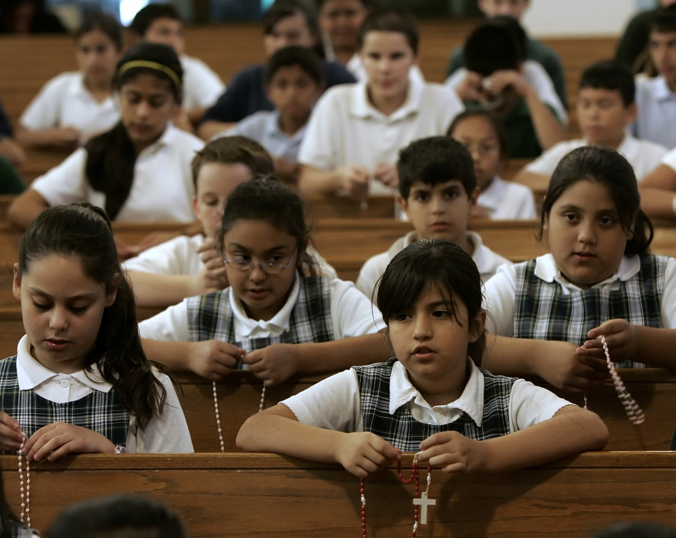 FILE - Catholic school students pray the rosary at St. Patrick's Catholic Church in Wichita, Kanasa, where the majority of parishioners are Hispanic. (AP Photo)