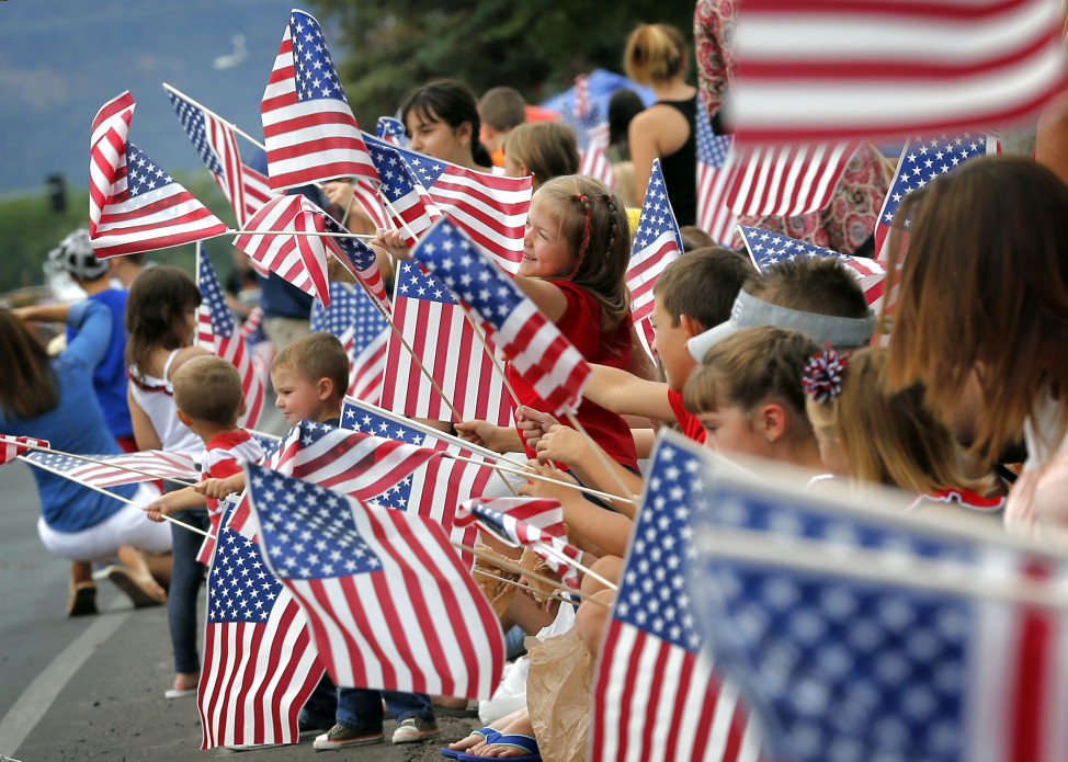 People wave flags as the Independence Day parade rolls down Main Street, July 4, 2014, in Eagar, Arizona. (AP Photo)