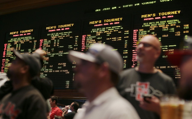 In this March 22, 2013, photo, bettors watch the odds for second-round NCAA tournament games displayed on a board at the Mirage hotel-casino Race & Sports Book in Las Vegas, Nevada. (AP Photo)