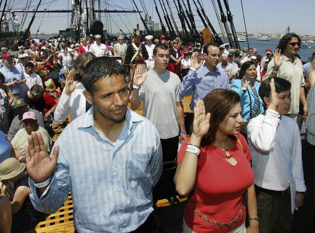 (File Photo) From left, Juan Quiroz, Rita Daaboul and Le Minh Le, take the oath of citizenship during a Naturalization ceremony aboard the USS Constitution, on the annual Fourth of July turnaround cruise in Boston Harbor. (AP Photo)