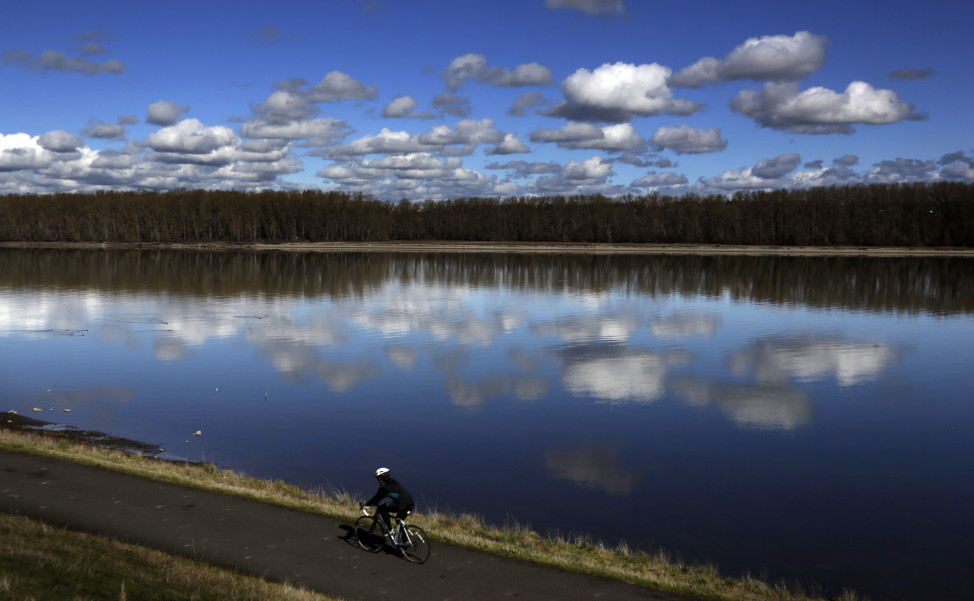 A bicyclist glides past the Columbia River in Portland, Oregon. (AP Photo)