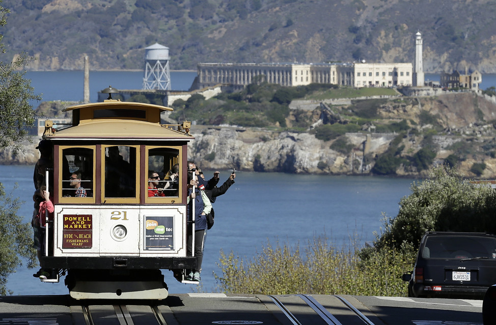 A cable car rolls up Hyde Street with Alcatraz Island in the background, in San Francisco, California. (AP Photo)