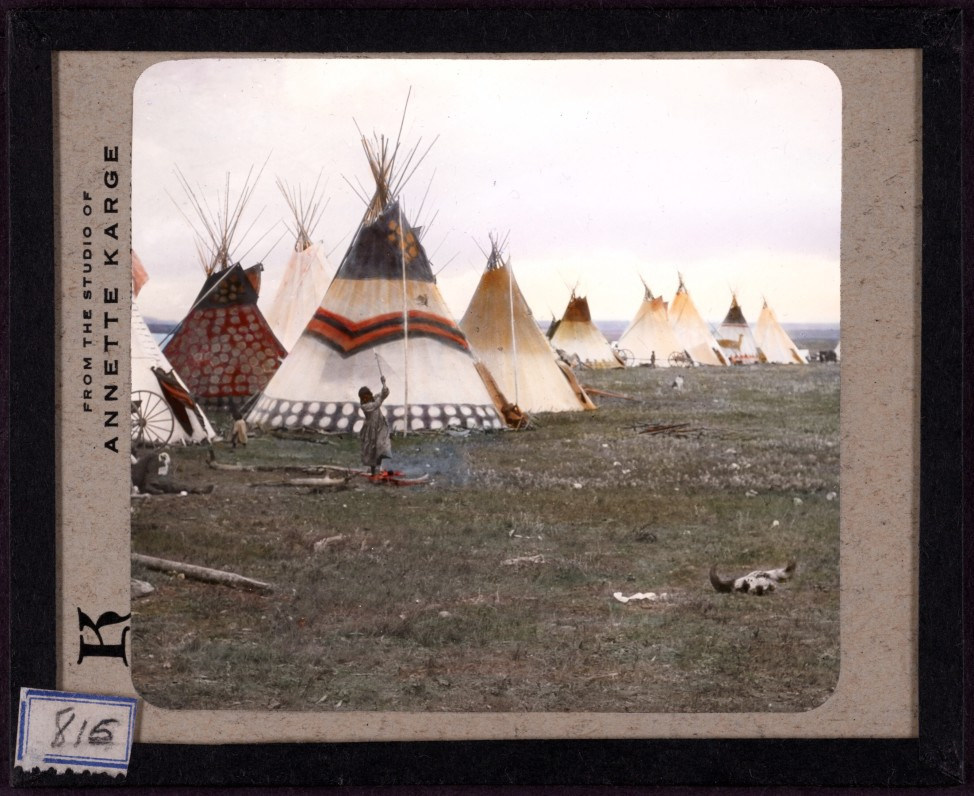 Woman chopping firewood, Eagle tipi in foreground, Star tipi on left. Hand-painted lantern slide by photographer Walter McClintock (1870-1949) of the Blackfoot Indians of Montana. (Yale Collection of Western Americana, Beinecke Rare Book and Manuscript Library)