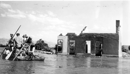 A salvage crew rafts through the town of St. Thomas near the ruins of a building as Lake Mead begins to submerge it in June 1938. (Lake Mead NRA Public Affairs via Flickr)