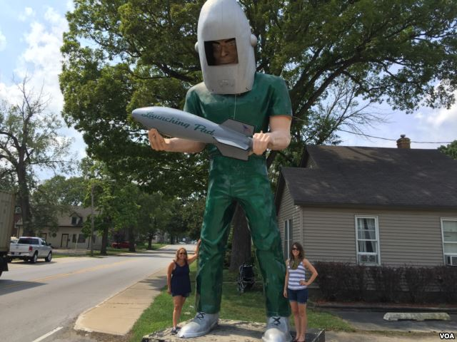 VOA reporters Caty Weaver (left) and Ashley Thompson (right) with the Gemini Giant in Wilmington, Illinois