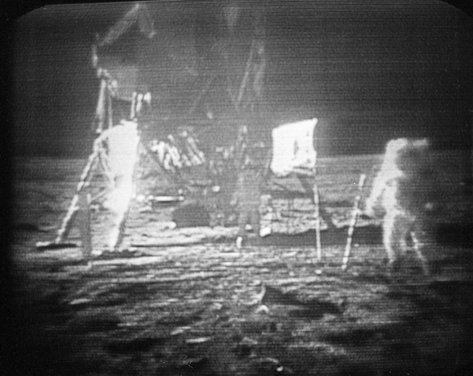 FILE - In this July 20, 1969 black-and-white file photo, taken from a television monitor, Apollo 11 astronaut Neil Armstrong, right, trudging across the surface of the moon.  Edwin E. Aldrin is seen closer to the craft. (AP Photo)