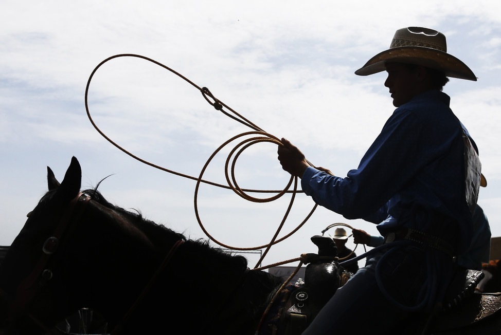 A cowboy waits to enter the arena for the calf roping competition at the International Finals Youth Rodeo, in Shawnee, Oklahoma, July 10, 2015. (AP Photo)