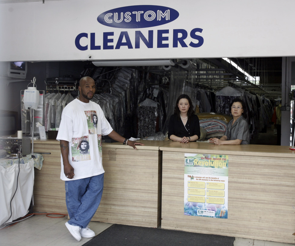 (File) Korean immigrant-owned Custom Dry Cleaners with store co-owner Chung Soo (R) and her daughter-in-law Choi Soo (C) behind the counter, with local customer Victory Hucks (L) in Washington, D.C. (Reuters)