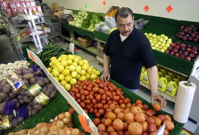 FILE -- Rae Alzaweny, owner of the Iraq Market grocery store, sorts produce in Dearborn, Michigan. (AP Photo)