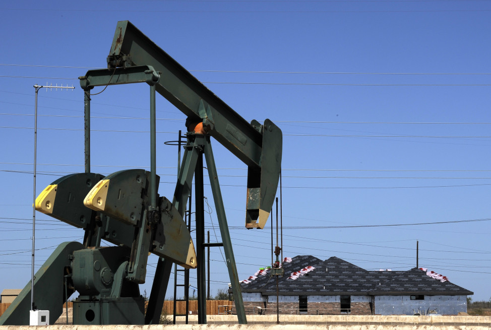 In this Monday, Sept. 23, 2013 photo, a pump jack works beside the site of new home construction, in Midland, Texas. (AP Photo)