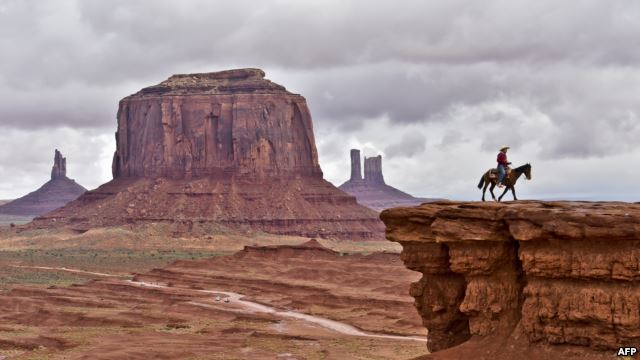 A Navajo man on a horse poses for tourists in front of the Merrick Butte in Monument Valley Navajo Tribal Park, Utah, in May 2015. (AFP PHOTO)