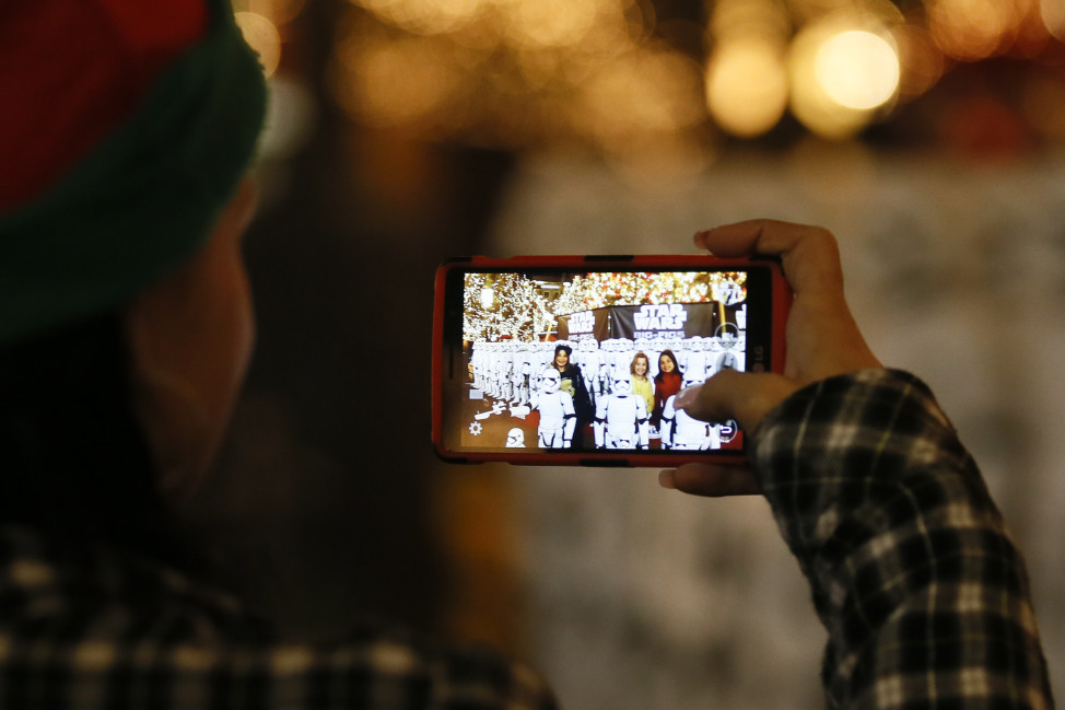 A woman uses a mobile device to take a photograph  Dec. 17, 2015, in Glendale, California. (AP Photo)