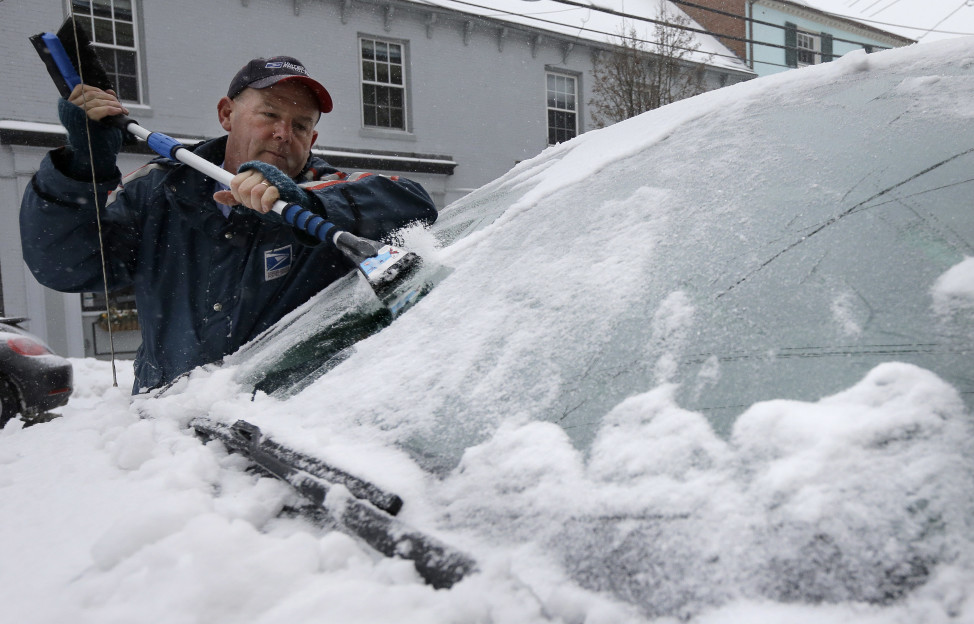 Postal worker Buddy Collins of Eliot, Maine, scrapes ice and snow from his windshield, Dec. 29, 2015, in Portsmouth, New Hampshire. (AP Photo)