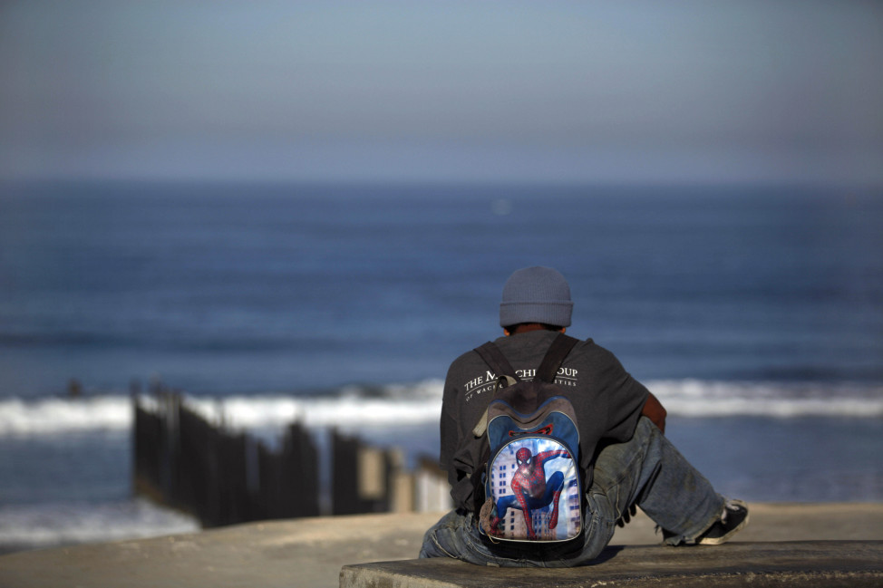 FILE -- A recently deported migrant from Seattle waits for a chance to cross to the U.S. near the US-Mexico border fence in Tijuana. (AP Photo)