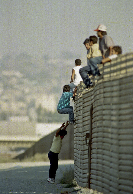 FILE - In this Oct. 14 1991 file photo, a group of illegal Mexican immigrants jump from a border fence to enter the United States, near Tijuana, Mexico. (AP Photo)