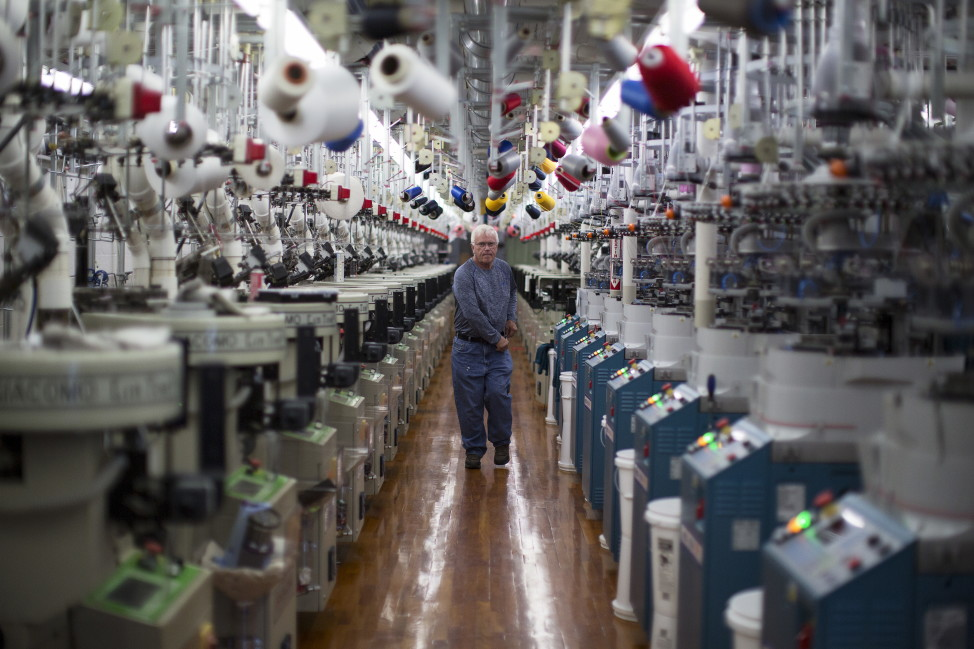 A worker walks between automatic sock knitting machines at Shankel's Hosiery manufacturing facility in Fort Payne, Alabama, Oct. 22, 2015. (Reuters)