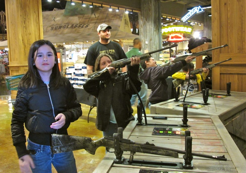 Chris Horsley of Texarkana, Texas, watches his children take aim at the shooting gallery in Bass Pro Shops at the Pyramid, a retail center in Memphis, Tennessee. From left are Jordana, Christa, Corbin and Mason. (C. Guensburg/VOA)