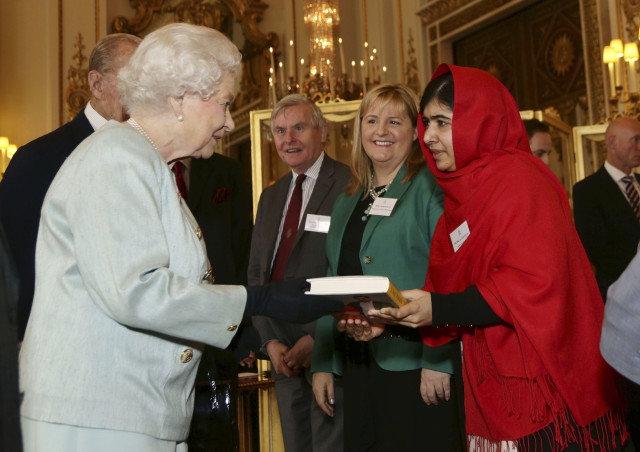 Malala Yousafzai gives a copy of her book to Britain's Queen Elizabeth during a Reception at Buckingham Palace in London