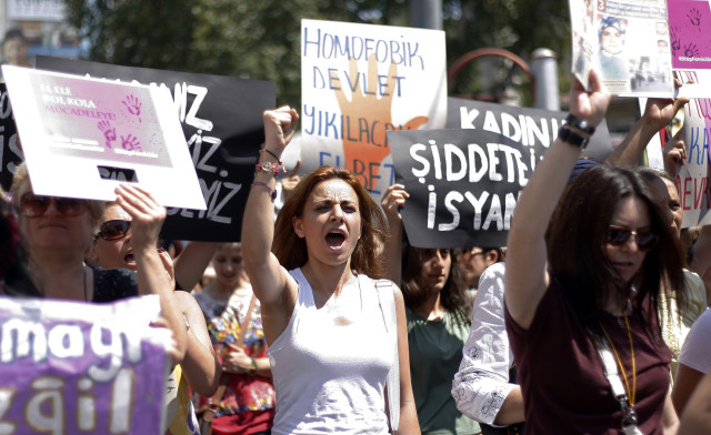 Women wave posters as they march in protest against domestic abuse, in Istanbul