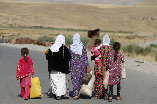 Women and children from the minority Yazidi sect, fleeing the violence in the Iraqi town of Sinjar, walk to a refugee camp after they re-entered Iraq from Syria at the Iraqi-Syrian border crossing in Fishkhabour