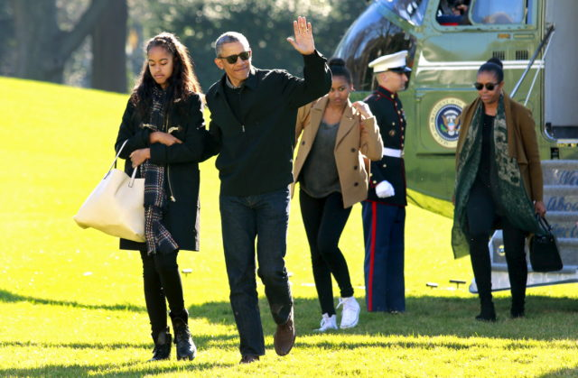 U.S. President Barack Obama waves as he walks with first lady Michelle Obama (R) and their daughters Malia (L) and Sasha on the South Lawn of the White House in Washington January 3, 2016. The Obama family returned from Hawaii, the president's home state, after concluding a 15-day holiday vacation. REUTERS/Yuri Gripas - RTX20VWO