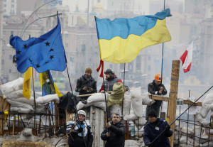 Ukrainian pro-EU demonstrators wave EU and Ukraine flags at a barricade in Independence Square in Kiev