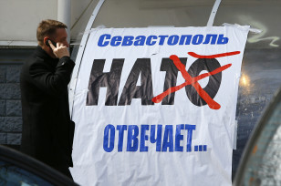 A man walks past an anti-NATO poster in the Crimean port of Sevastopol