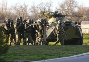 Armed men, believed to be Russian servicemen, take cover behind an armoured vehicle as they attempt to take over a military airbase in the Crimean town of Belbek near Sevastopol