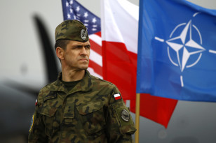 A Polish soldier stands near U.S. and Poland's national flags and a NATO flag as U.S. paratroopers from the U.S. Army's 173rd Infantry Brigade Combat Team arrived to participate in training exercises with the Polish army in Swidwin