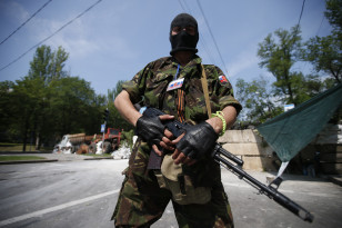 Member of a newly-formed pro-Russian armed group called the Russian Orthodox Army stands guard at a barricade near Donetsk airport