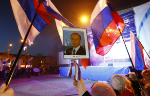 A woman holds a portrait of Russia's President Putin during celebrations on the main square of?the Crimean city of?Simferopol