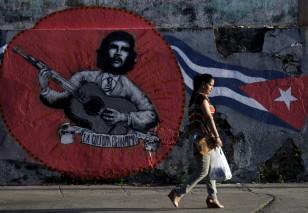 "A woman walks past graffiti of revolutionary hero Ernesto ""Che"" Guevara and a Cuban flag of mexican artistic group Azaro for the 12th Havana Biennial, in Havana"