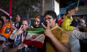 Iranians gesture as they celebrate in the street following a nuclear deal with major powers, in Tehran