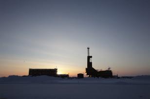 Prudhoe Buxtasında neft buruğunun arxasında günəş qürub edir.
